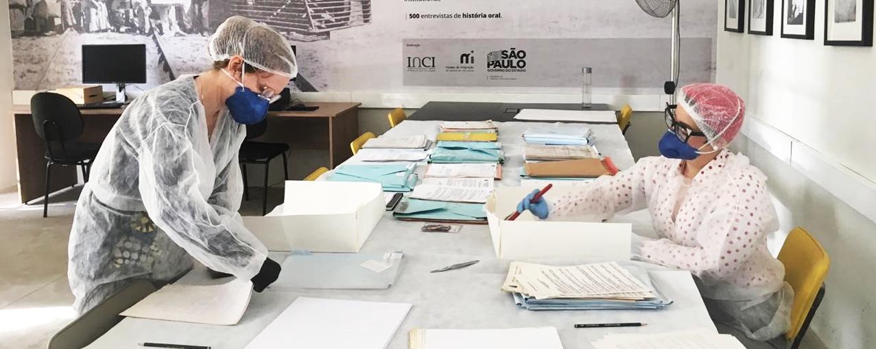 Colaboradoras do Museu estão mexendo em documentos do arquivo, utilizando capas, máscaras e luvas