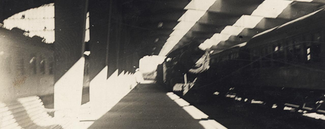 Fotografia de acervo, em preto e branco, mostrando a estação de trem Roosevelt, com bancos, pilastras e dois trens, um chegando e outro parado