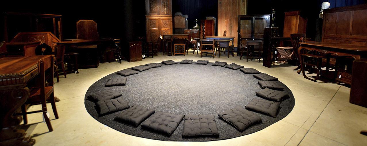 Móveis de madeira estão dispostos em um semicírculo com um tapete redondo cinza escuro no chão e almofadas da mesmas cor em cima dele