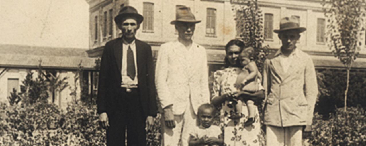 Fotografia de acervo, em sépia, mostrando uma família formada por três homens, uma mulher e duas crianças, posando com a Hospedaria do Brás e um jardim de fundo