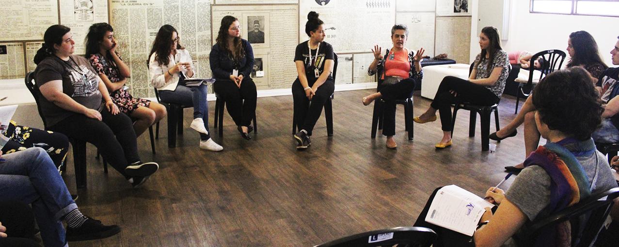 A imagem mostra mulheres, sentadas em roda, conversando em uma sala