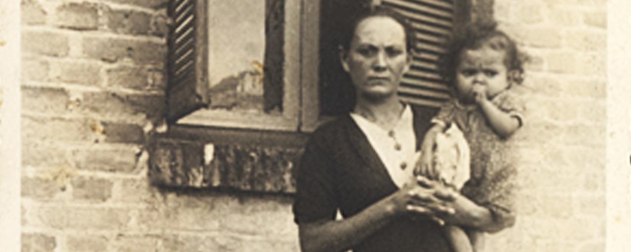 A imagem mostra uma mulher segurando um bebê, em frente à janela de uma casa