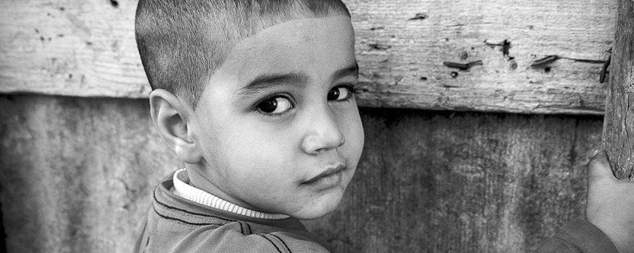 Em preto e branco, a imagem mostra um menino olhando de lado para a foto
