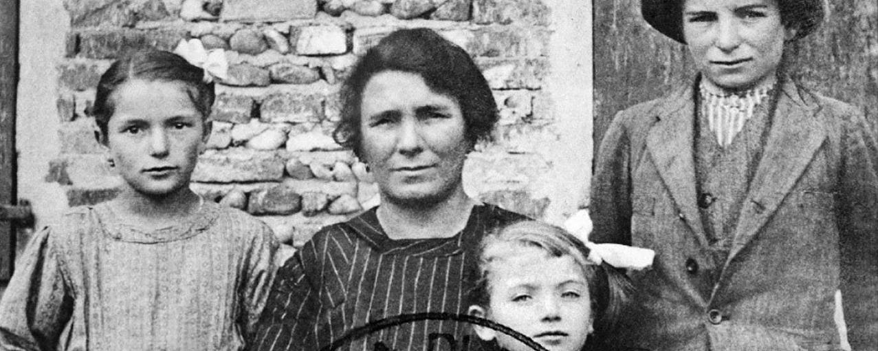 Três crianças e uma mulher posam para fotografia que está em preto e branco