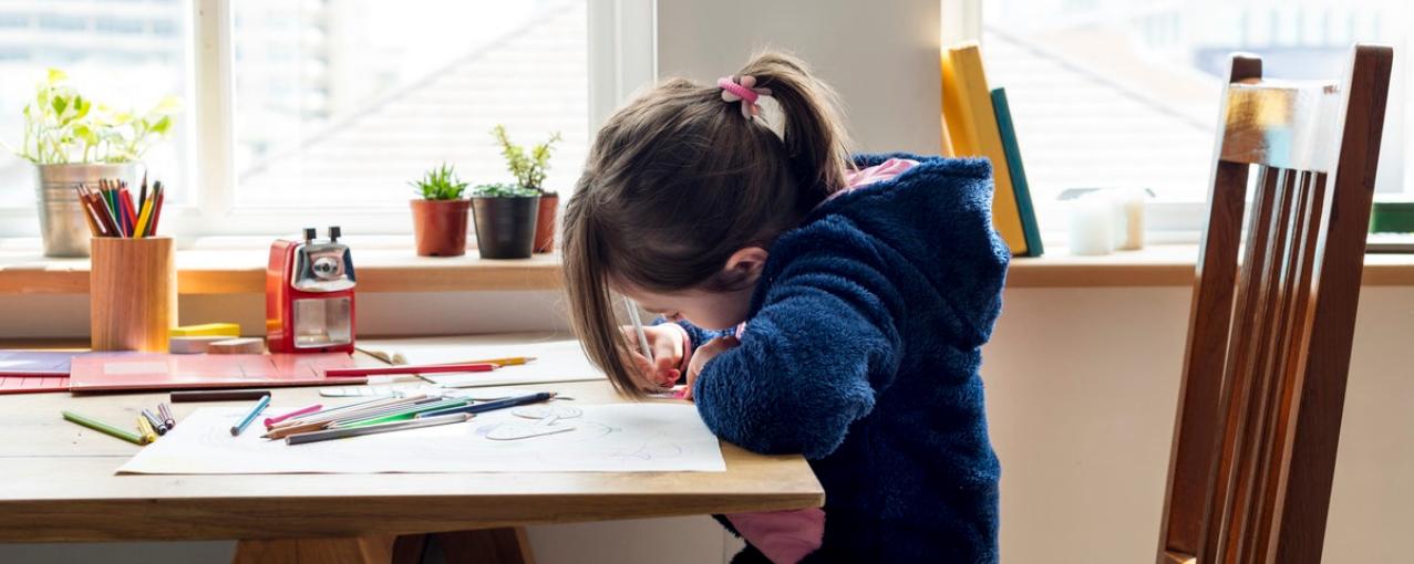 Criança em uma mesa escrevendo