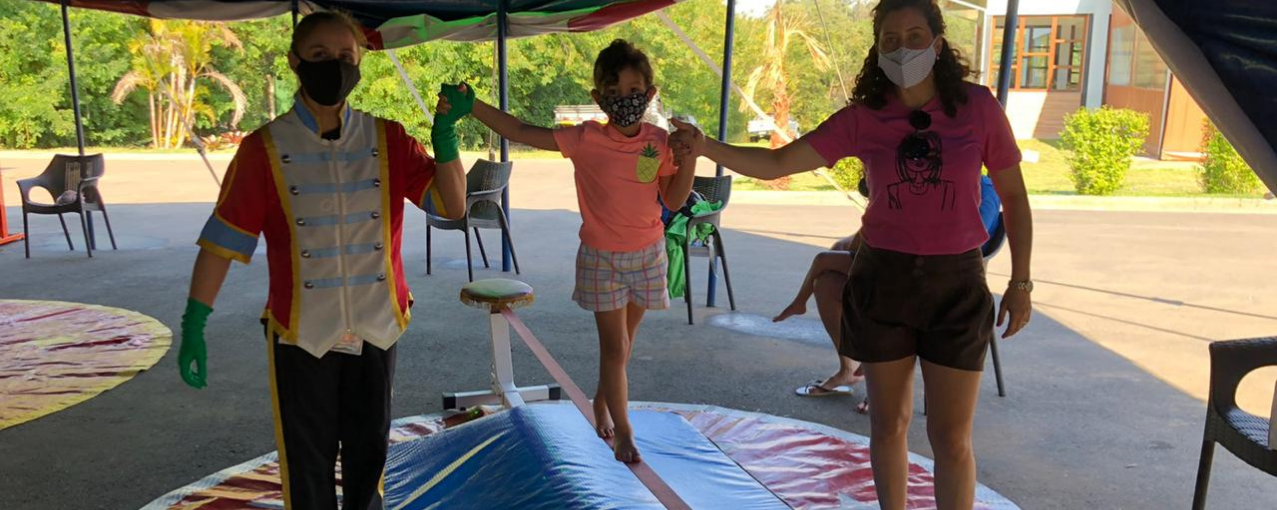 Dois adultos dando apoio a uma criança para se equilibrar em elástico